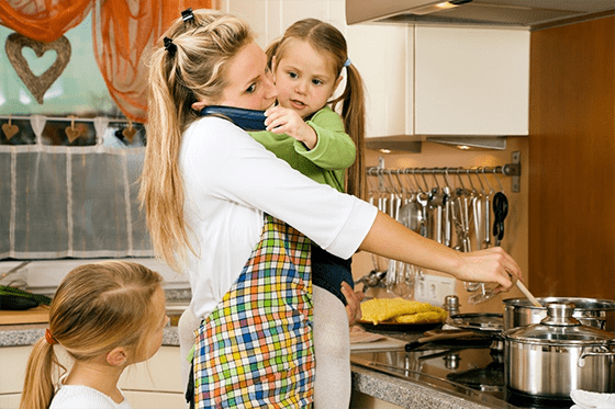 Mum holding child cooking and on the phone